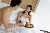 Couple having breakfast in bed - Asia Images Group