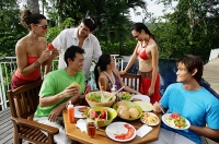 Young adults having a meal on patio - Asia Images Group