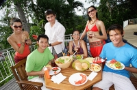 Young adults having a meal on patio, smiling at camera - Asia Images Group