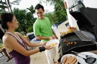 Couple grilling food on barbeque - Asia Images Group