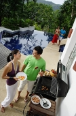 Couple grilling food over barbeque - Asia Images Group