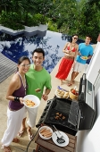 Couples at barbeque party, smiling at camera - Asia Images Group