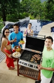 Couples having a barbeque, looking at camera - Asia Images Group