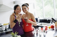Two women in kitchen, drinks in hand, smiling at camera - Asia Images Group