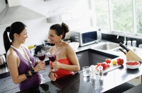 Two women standing in kitchen, holding wine glasses - Asia Images Group