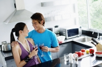 Couple standing in kitchen, holding wine glasses - Asia Images Group