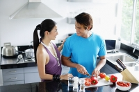 Couple standing in kitchen, man chopping vegetables - Asia Images Group