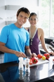 Couple standing in kitchen, looking at camera, man holding knife, chopping vegetables - Asia Images Group