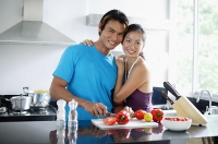 Couple standing in kitchen, looking at camera, woman embracing man - Asia Images Group