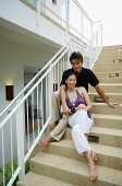 Couple sitting on staircase, smiling at camera - Asia Images Group