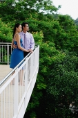 Couple standing on balcony, side view - Asia Images Group