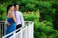 Couple standing on balcony, looking away, side view - Asia Images Group