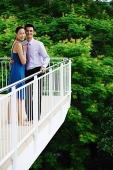 Couple standing on balcony,  looking at camera - Asia Images Group
