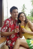 Couple side by side, holding drinks - Asia Images Group