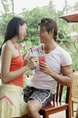 Couple with drinks, looking at each other - Asia Images Group