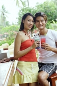 Couple at beach bar, holding drinks, looking at camera - Asia Images Group