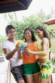 Young adults at beach bar toasting with drinks - Asia Images Group