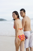 Couple on beach, looking over shoulder at camera - Asia Images Group