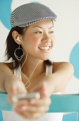 Young woman wearing beret, listening to MP3 player - Asia Images Group