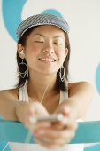 Young woman wearing beret, listening to MP3 player, eyes closed - Asia Images Group