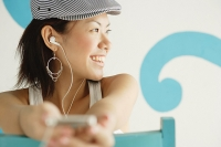 Young woman wearing beret, listening to MP3 player, looking away, smiling - Asia Images Group