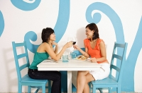 Young women in cafe, having lunch, toasting with wine glasses - Asia Images Group