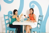 Young women in cafe, toasting with wine glasses, smiling at camera - Asia Images Group