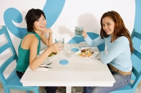Young women having lunch in cafe, raising water glasses to camera - Asia Images Group