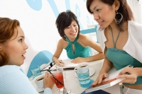 Young women talking over drinks in cafe - Asia Images Group