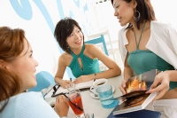 Young women talking over drinks in cafe, one woman holding book - Asia Images Group