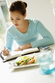 Young woman sitting at table, food next to her, writing in notebook - Asia Images Group