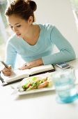 Young woman sitting at table, writing in notebook - Asia Images Group