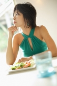 Young woman at table, looking away, plate of salad in front of her - Asia Images Group