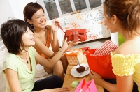 Young women at home, celebrating birthday, opening gifts - Asia Images Group