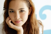 Young woman looking at camera, hand on chin - Asia Images Group