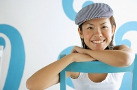 Young woman wearing beret, leaning on chair, looking at camera - Asia Images Group