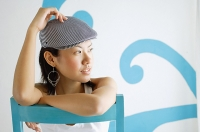 Young woman wearing beret, looking away, hand on head - Asia Images Group