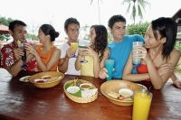 Young adults hanging out at beach bar - Asia Images Group