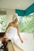Woman in towel, sitting at edge of bath tub - Asia Images Group