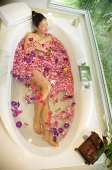 Woman taking a bath, flowers floating in water, high angle view - Asia Images Group