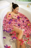 Woman in bathtub, surrounded by flowers, looking at camera - Asia Images Group