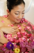 Woman in bathtub, flowers floating in water - Asia Images Group
