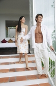 Couple walking down steps outside of bedroom, holding hands - Asia Images Group