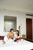Couple sitting on bed, eating breakfast - Asia Images Group