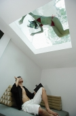 Man waving at woman in swimming pool through the skylight - Asia Images Group