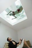 Man looking at woman in swimming pool through the skylight - Asia Images Group