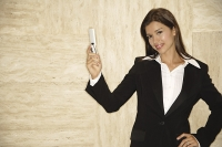 Businesswoman with mobile phone, looking at camera, hand on hip - Asia Images Group