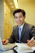 Businessman with laptop open on table, smiling at camera - Asia Images Group