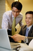 Businessmen working together, looking at laptop - Asia Images Group