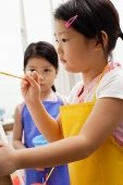 Girl with paintbrush, another girl standing next to her - Asia Images Group